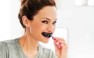 Девушка чистит зубы активированным углем