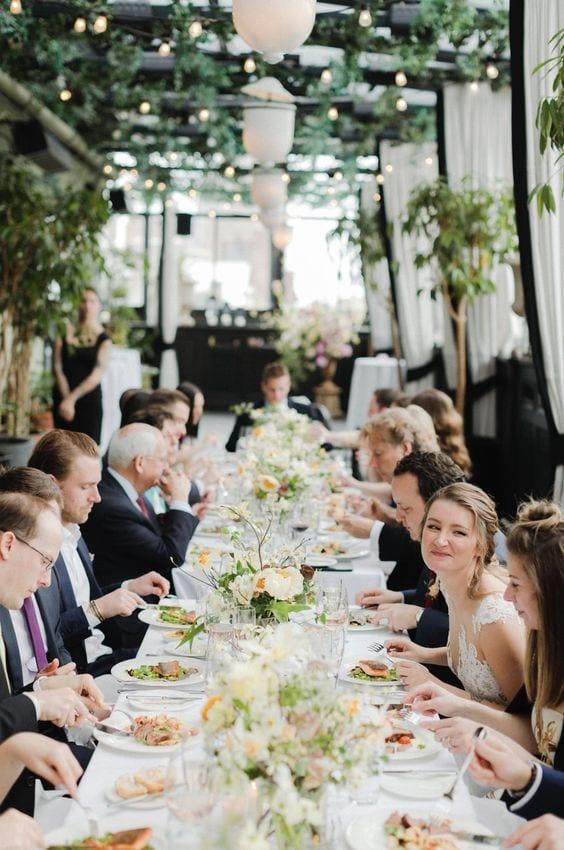 Mesa branca com convidados em volta.