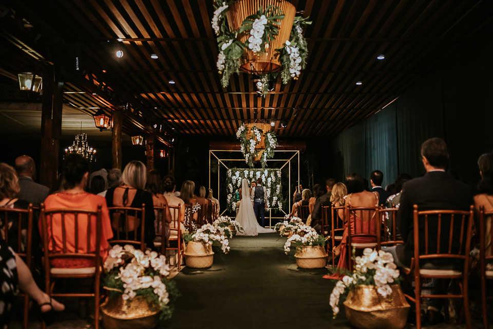 Convidados sentados em cadeiras de madeira marrom, noivos sendo casados.