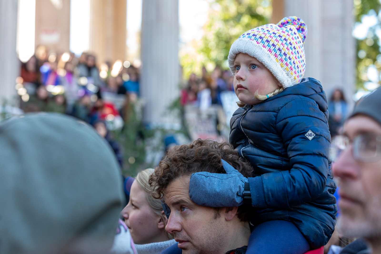 A girl watches speakers at the climate strike from the shoulders of a man. Photo: Andy Bosselman, Streetsblog Denver