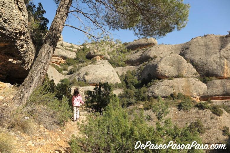 niña por sendero entre rocas y arboles