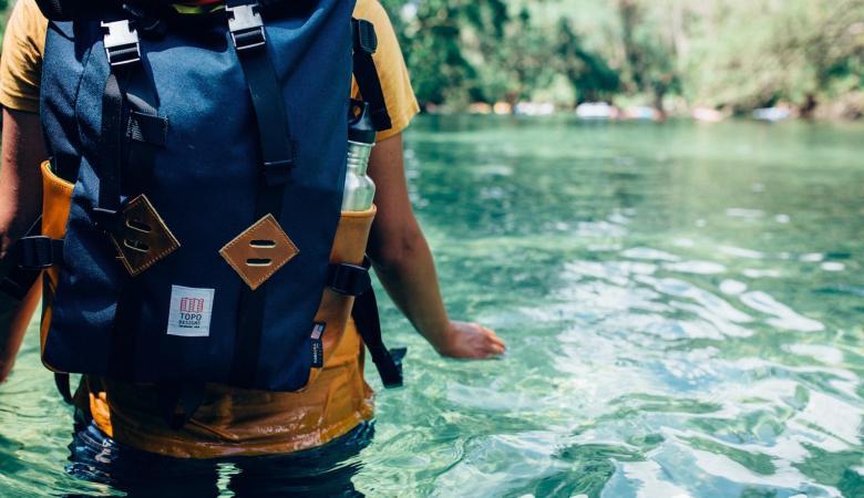 persona dentro de río cristalino con mochila en espalda