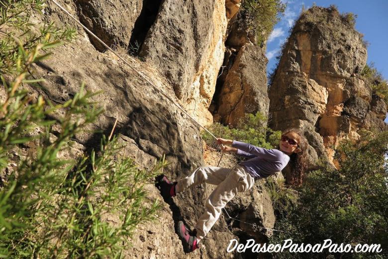 Niña pasando por las rocas ayudada por una soga en la pared de roca