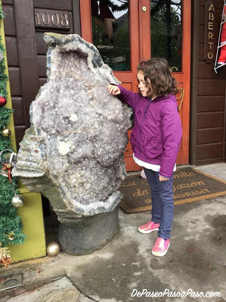 Niña observando una piedra semi preciosa gigante
