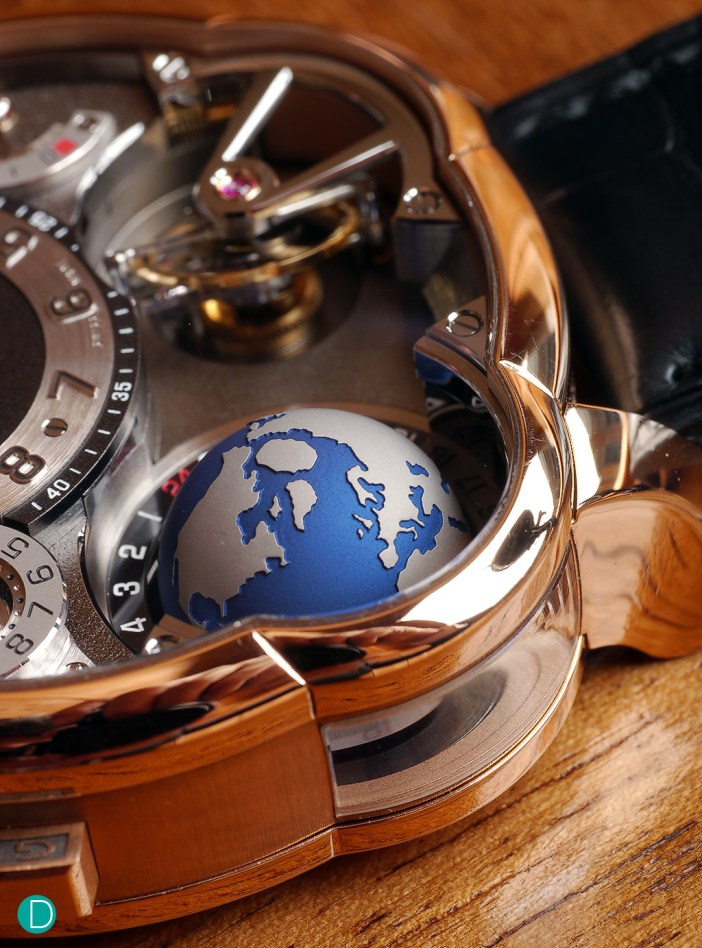 A close up to the globe. Details are particularly interesting. Note the window on the case band to allow light into the globe, symbolizing the sun's rays for daylight on the globe.