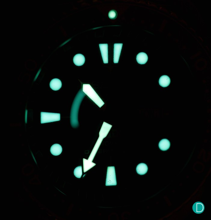 The very bright lume of the Seiko PADI Automatic Diver. Note the bright dot on top of the triangle is the center marker for the rotating bezel. At 3 o'clock, the luminous marker is absent as the space is taken by an aperture showing the day and date.