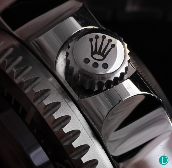 The crown is massive and is laser engraved with the crown logo and the three dots which signifies a 904L Stainless Steel case with Triplock.
