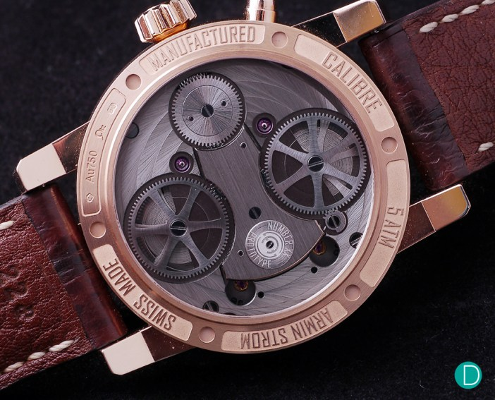 The caseback shows the twin barrels and the dual train.