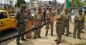Satpol PP bersama Polres dan Kodim 0508/Depok menurunkan kabel udara di Jalan Margonda Depok.