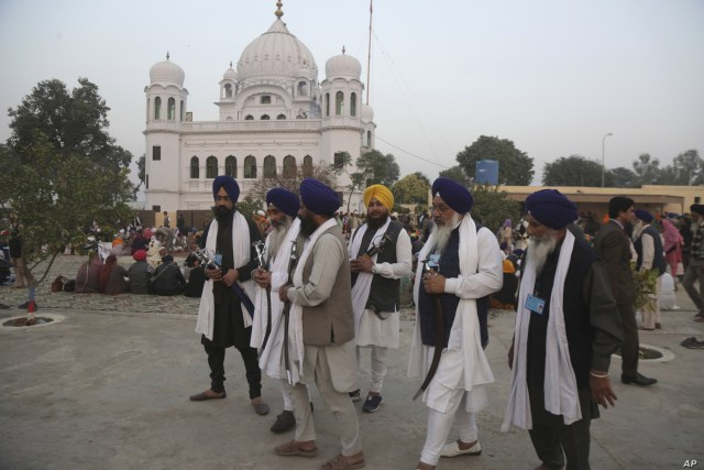 FILE - In this Nov. 28, 2018 file photo, Indian Sikh pilgrims visit  Gurdwara Darbar Sahib, the shrine of their spiritual leader Guru Nanak Dev in Kartarpur, Pakistan.  Officials from India and Pakistan met Thursday, March 14, amid easing tensions…