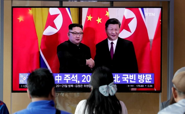 In this June 18, 2019 photo, people watch a TV news program reporting about Chinese President Xi Jinping's state visit to North Korea with a file footage of Chinese President Xi Jinping and North Korean leader Kim Jong Un, at the Seoul Railway…