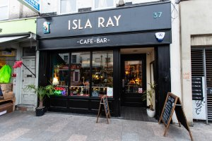 Isla Ray café bar from outside showing the shop front painted in black with Isla Ray in wooden lettering in an Art Deco font