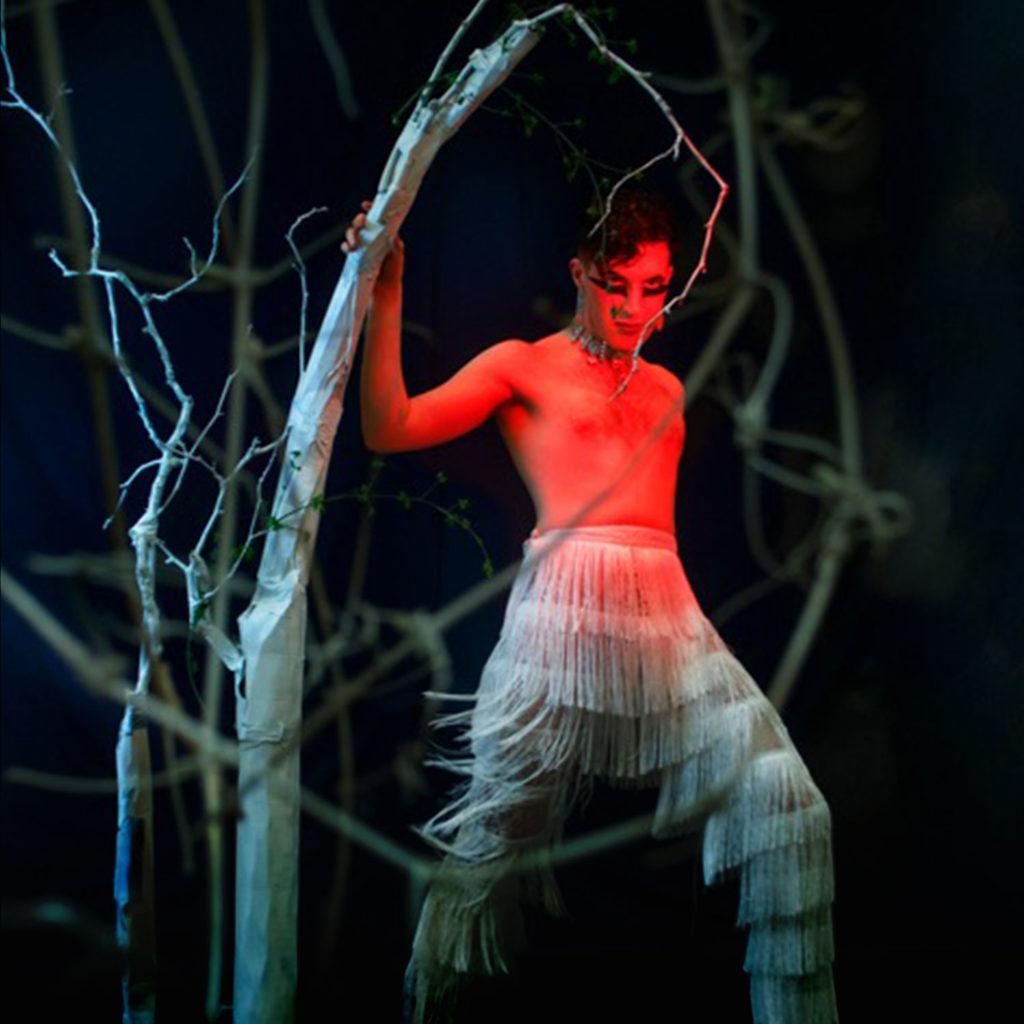 Sainte Torrente lit in red, standing against a dark woodland background