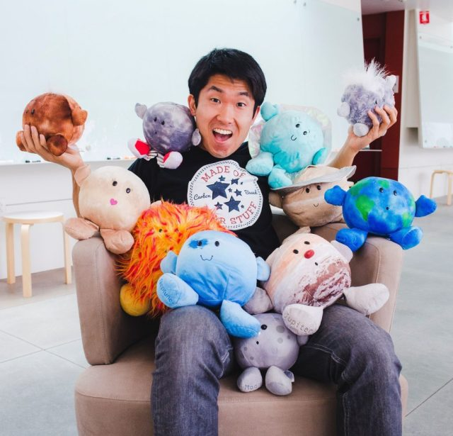 Postdoctoral scholar Michael Wong sitting with stuffed planets.