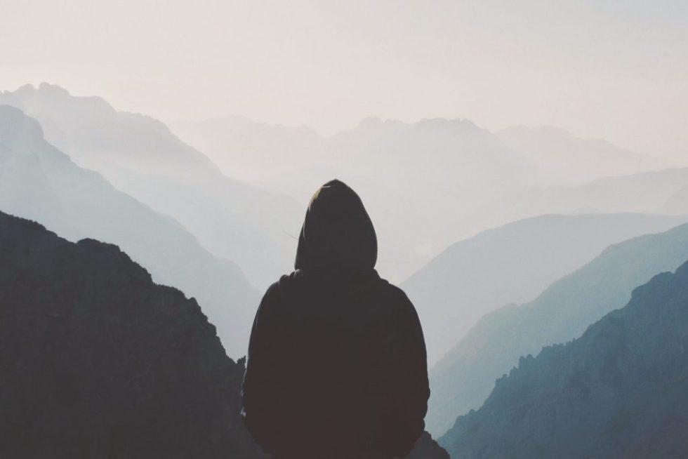 Mann steht vor weiter Landschaft.