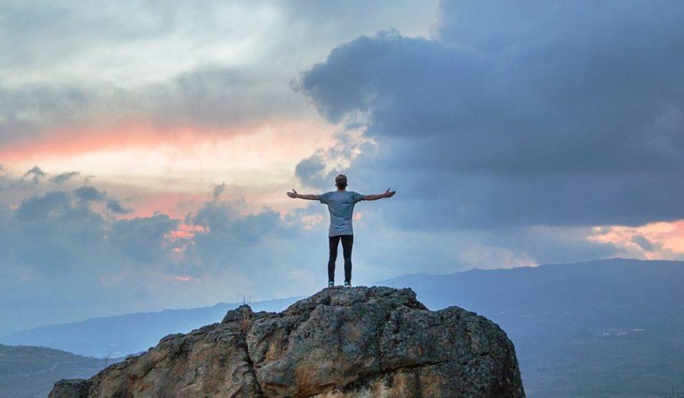 Sportler steht auf dem Gipfel eines Hügels. Coaching Mentaltraining Beratung