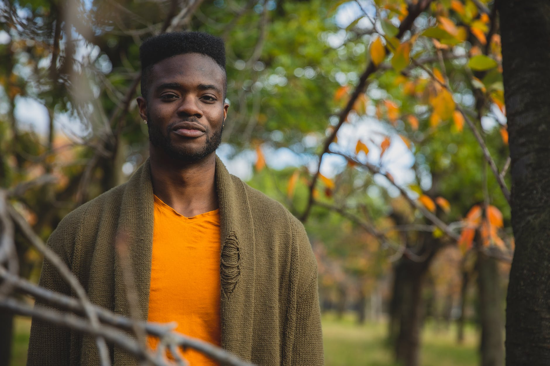 smiling young ethnic male standing in autumnal garden near bright trees