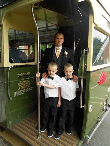 Twin boys dressed in shirts with bow ties stands with a best man on an old traditional bus.