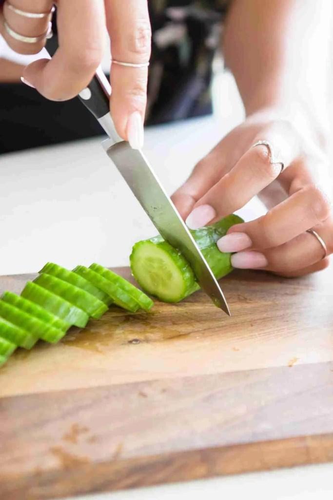 woman slicing up a cucumber