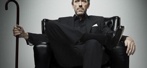 Sentado con traje negro, rostro impávido, piernas cruzadas.