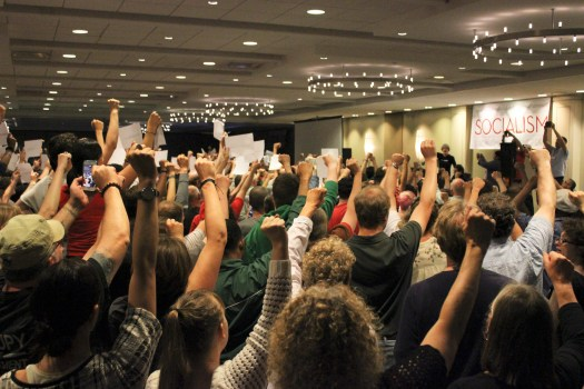 Socialists at conference with fists up.