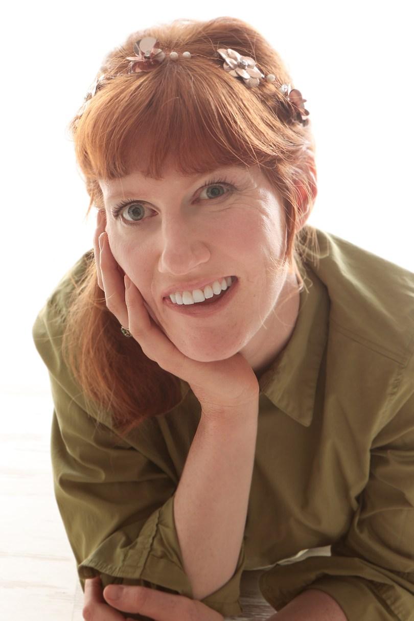 Die Autorin trägt ein grünes Hemd und lacht in die Kamera