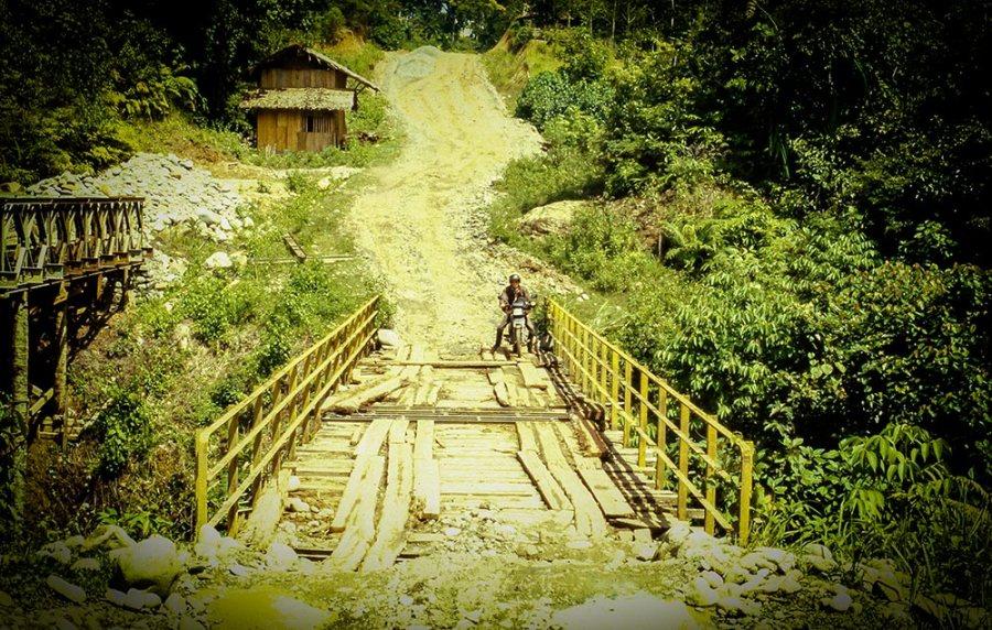 Mit dem Motorrad auf einer Lehmpiste an einer klapprige Brücken im Urwald.