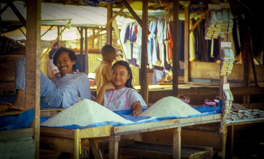 Marktstand mit zwei Reishaufen. Ein Mann liegt lässig auf einem Stand. Eine Frau sitzt daneben. Beide lächeln.