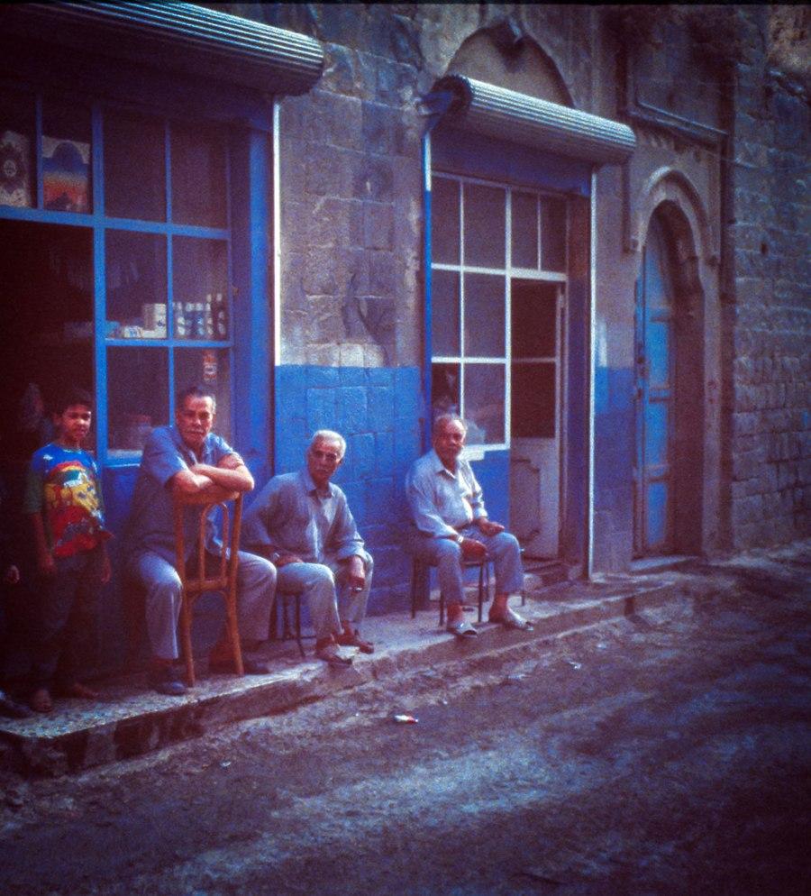 Strassenszene: 3 Herrn und ein Junge vor einem Ladengeschäft