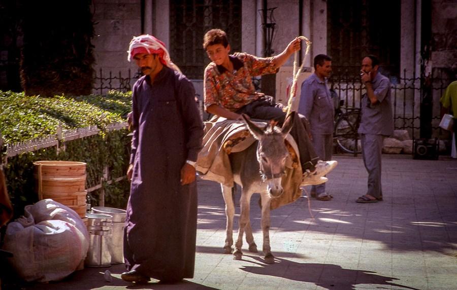 Händler in traditioneller Tracht, Junge auf einem Esel, 2 Herren in uniformähnlicher Kleidung