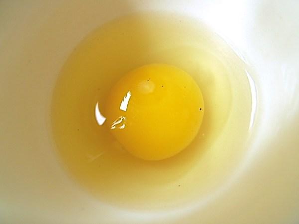 Das Wachtelei zum Pochieren in einen Eierbecher schlagen