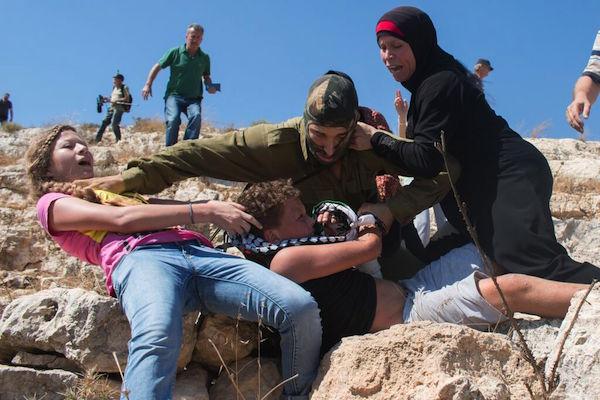 Ahed (esq.), Nawal (direita) e Nariman Tamimi (atrás) defendem Mohammed, 12 anos, que teve um braço quebrado por um soldado israelense. Foto: Karam Salim