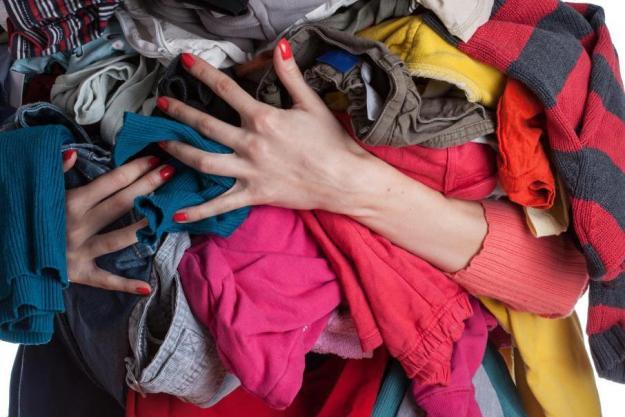 woman-holding-pile-of-clothes, melhores souvenires de viagem