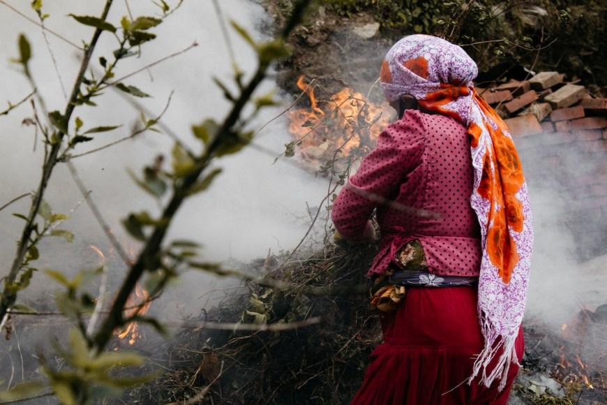 Mujer nepalí revivando un fuego de deshechos, Nepal