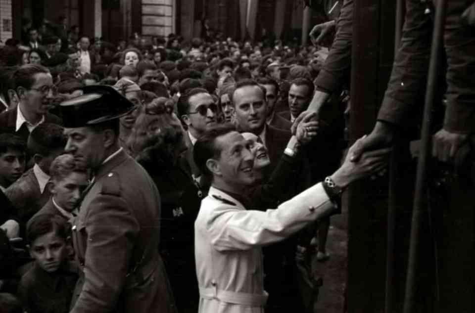 Dionisio Ridruejo con chaqueta blanca saludando a los miembros de la División Azul en San Sebastián. 1942. Fondo Marín-Kutxa Fototeka. Wikimedia Commons
