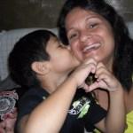Kadu beija a mamãe Debora no rosto, enquanto faz um sinal de coração com as mãos. Debora sorri emocionada.
