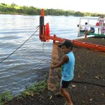 Kadu de short, camiseta e boné, segurando uma vara de pescar, nas margens de um rio, todo sorridente.