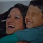 Kadu sorri de olhos fechados, abraçando a mãe pelo pescoço. Debora sorri de contentamento.
