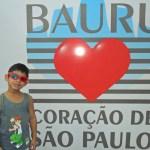 Kadu de óculos escuros de aro vermelho, em frente a um painel, onde está escrito: Bauro, coração de São Paulo.