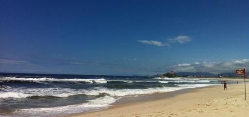 Imagem da praia de Itauna, em Saquarema. O céu azul com poucas nuvens, o mar num tom azul profundo, revolto, e a areia bege clara. Há também uma placa vermelha indicando sinal de perigo.