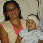 Kadu após a cirurgia, com 1 ano, usando o curativo de turbante, no colo da mamãe Debora