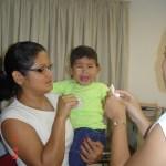 Kadu, no colo da mãe, chorando no dia da ativação, um mês após a cirurgia.