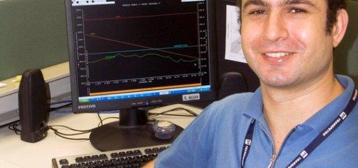 Foto de um homem jovem com um crachá no pescoço, sentado em frente a um computador em ambiente de trabalho, olhando para frente e sorrindo.