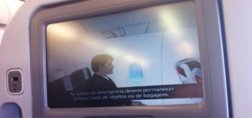 Imagem da tela individual da poltrona do avião da Avianca, com video de instruções de segurança legendado em português e inglês.