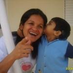 Kadu roubando um beijo da bochecha da mamãe, que ri e aponta para a câmera, em vão.