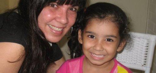 Foto de Mônica, sorrindo, ao lado da pequena Milena, que também sorri para a câmera.