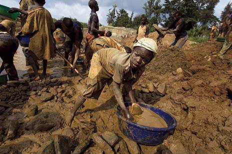 Niño congolés trabajando con sus manos en busca de coltán