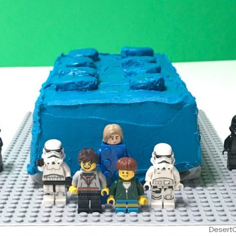 blue birthday cake shaped like a LEGO brick with Lego minifigures standing in front of it