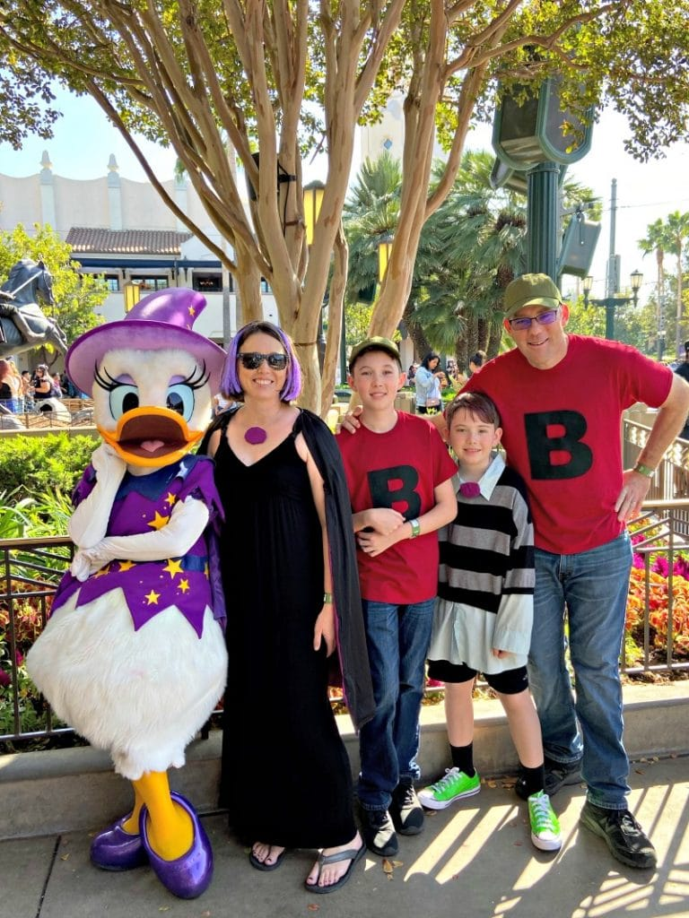 DuckTales Costume Family Meets Daisy Duck dressed as a witch at Disneyland's Oogie Boogie Bash