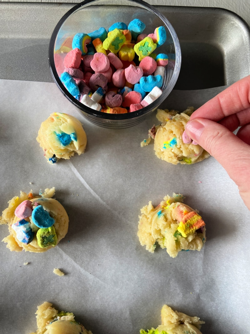 hand placing Lucky Charms marshmallows on top of drops of cookie dough